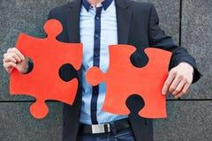 Homem de negócio que guarda partes vermelhas do enigma de serra de vaivém Fotos de Stock