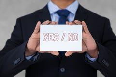 Homem de negócio que guarda um cartão com texto sim/não Imagem de Stock