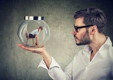 Homem de negócio que guarda um frasco de vidro com uma mulher de negócio triste nova prendida nele imagem de stock royalty free