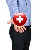 Homem de negócio que guarda um símbolo da cruz vermelha Imagem de Stock Royalty Free