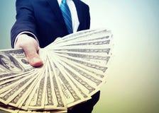 Homem de negócio que indica uma propagação do dinheiro imagens de stock royalty free