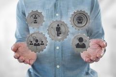 Homem de negócio que interage com os povos em gráficos das rodas denteadas contra o fundo branco Imagem de Stock Royalty Free