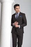 Homem de negócio que levanta perto da coluna branca no fundo cinzento do estúdio imagem de stock royalty free