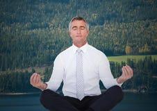 Homem de negócio que medita contra árvores e rio Foto de Stock