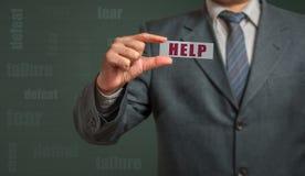 Homem de negócio que mostra o cartão com texto - ajuda Imagem de Stock Royalty Free