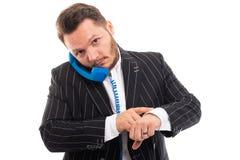 Homem de negócio que mostra o relógio de pulso e que fala no telefone azul do receptor foto de stock
