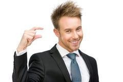 Homem de negócio que mostra a pequena quantidade de algo Imagens de Stock