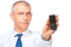 Homem de negócio que mostra um telefone móvel fotografia de stock royalty free
