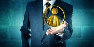 Homem de negócio que oferece um ícone dourado do trabalhador de escritório Fotografia de Stock
