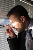 Homem de negócio que olha através das cortinas de indicador Fotos de Stock Royalty Free