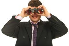 Homem de negócio que olha com binocular Fotos de Stock
