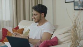 Homem de negócio que olha o sofá dos papéis dos dados financeiros em casa Homem de neg?cios feliz filme
