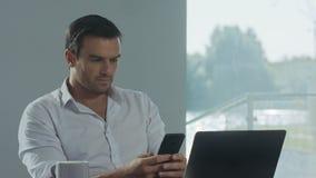 Homem de negócio que olha o telefone celular no lugar de trabalho Homem concentrado que tem a ruptura video estoque