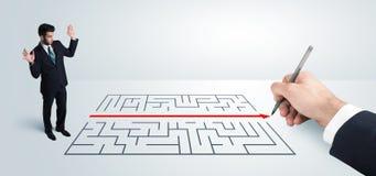 Homem de negócio que olha a solução à mão do desenho para o labirinto Fotografia de Stock