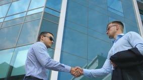 Homem de negócio que passa uma pasta preta a seu sócio Os colegas agitam as mãos exteriores no fundo da cidade Dois jovens Fotos de Stock Royalty Free