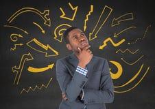 Homem de negócio que pensa contra a parede cinzenta com os gráficos amarelos da seta Imagem de Stock Royalty Free