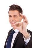 Homem de negócio que pisc com sinal aprovado Imagens de Stock Royalty Free