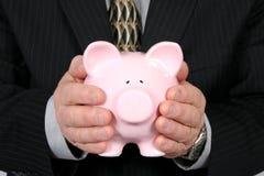 Homem de negócio que prende o banco Piggy Fotografia de Stock Royalty Free