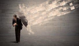 Homem de negócio que protege com o guarda-chuva contra o vento dos papéis imagens de stock royalty free
