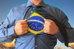 Homem de negócio que puxa seu t-shirt aberto, mostrando a Brasil a bandeira nacional Céu azul com as nuvens no fundo imagem de stock
