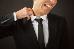 Homem de negócio que puxa sua camisa de seu pescoço Imagem de Stock