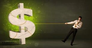 Homem de negócio que puxa um sinal de dólar verde grande Foto de Stock Royalty Free