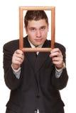 Homem de negócio que quadro sua cara com quadro de madeira Imagem de Stock