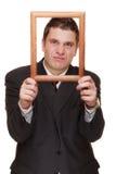 Homem de negócio que quadro sua cara com quadro de madeira imagens de stock royalty free