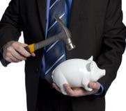 Homem de negócio que quebra o banco piggy com martelo Fotografia de Stock Royalty Free
