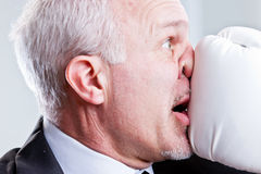 Homem de negócio que recebe um perfurador na cara Fotos de Stock Royalty Free