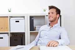 Homem de negócio que relaxa no escritório imagem de stock
