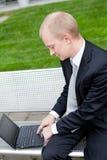 Homem de negócio que senta o trabalho exterior com caderno fotografia de stock royalty free