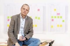 Homem de negócio que senta-se em sua mesa fotos de stock