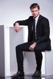 Homem de negócio que senta-se em uma cadeira ao descansar sua mão foto de stock