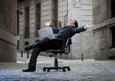 Homem de negócio que senta-se na cadeira do escritório na rua com computador imagem de stock