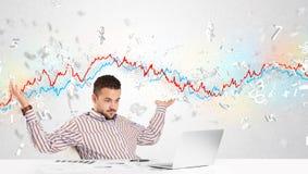 Homem de negócio que senta-se na tabela com gráfico do mercado de valores de ação Foto de Stock