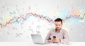 Homem de negócio que senta-se na tabela com gráfico do mercado de valores de ação Imagens de Stock
