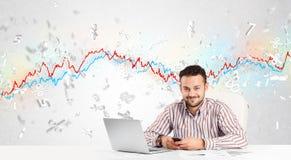 Homem de negócio que senta-se na tabela com gráfico do mercado de valores de ação Fotografia de Stock Royalty Free