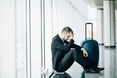 Homem de negócio que senta-se no aeroporto terminal no assoalho com atraso de voo da mala de viagem, toque de duas mãos na cabeça fotografia de stock royalty free