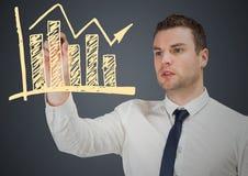 Homem de negócio que tira a garatuja amarela do gráfico contra o fundo cinzento Fotos de Stock