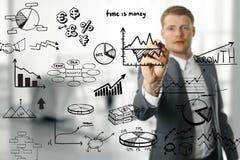 Homem de negócio que tira gráficos e cartas diferentes Imagens de Stock