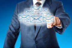 Homem de negócio que toca em uma nuvem de muitos ícones do email Imagens de Stock