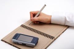 Homem de negócio que toma notas com telefone de pilha Fotografia de Stock