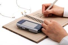 Homem de negócio que toma notas da reunião com telefones e vidros de pilha Fotos de Stock Royalty Free