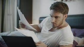 Homem de negócio que trabalha com papéis no sofá na noite Funcionamento focalizado do homem de neg?cios filme