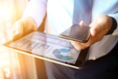Homem de negócio que trabalha e que analisa figuras financeiras no gráficos em uma tabuleta e em um telefone celular fotografia de stock