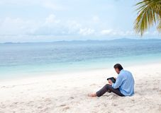 Homem de negócio que trabalha na praia com Ipad