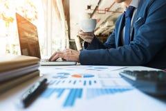 Homem de negócio que trabalha no escritório com dat do portátil, da tabuleta e do gráfico Fotografia de Stock Royalty Free