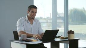 Homem de negócio que trabalha no laptop Freelancer positivo que prepara documentos vídeos de arquivo