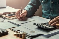 homem de negócio que usa a calculadora para calcular com escrita dos dados Fotografia de Stock Royalty Free